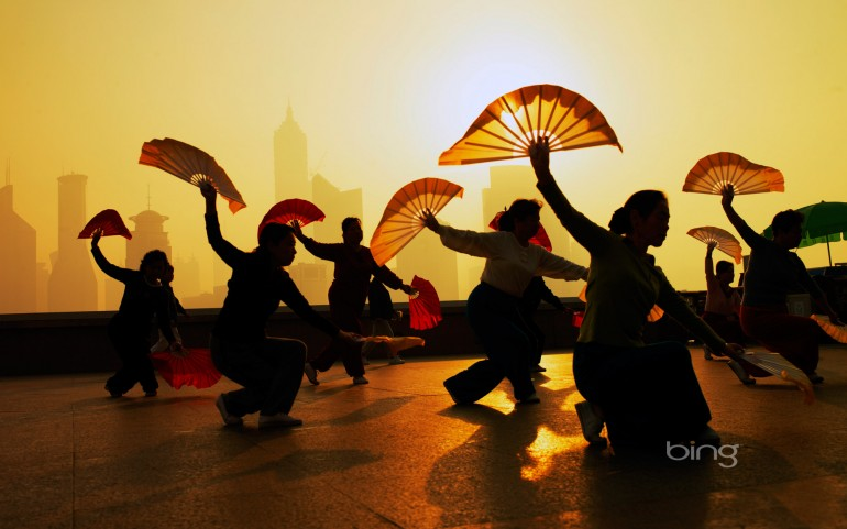 Women fan dancing on the Bund overlooking the Pudong district, Shanghai, China