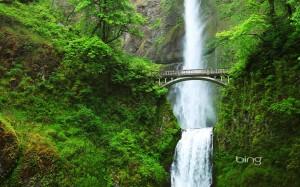 a waterfall behind a bridge